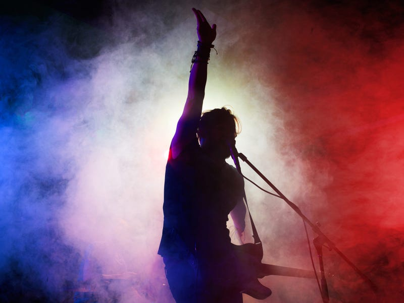 Silhouette of man playing guitar with smoky background