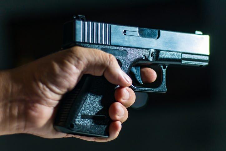 Man's hand holding a handgun on black