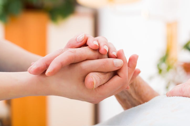 A caregiver holding a person's hand.