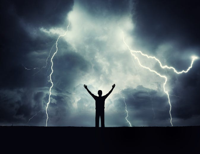A man silhouette on a storm background. Lord of the lightning. Background on the theme of survival, religion, philosophy, psychology.