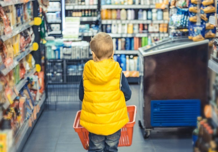 Back view of kid buying groceries at supermarket.