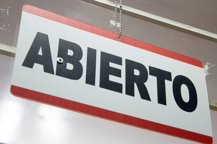 An spanish open sign hanging in a store. Abierto meaning open.