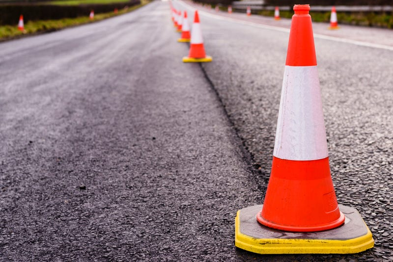 Row of traffic cones along the middle of a road being resurfaced