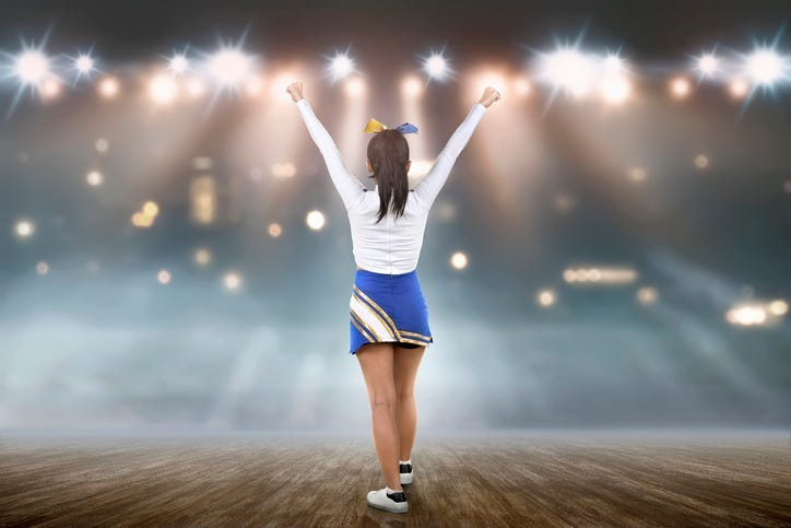 ear view of asian cheerleader in white and blue suit on the stage