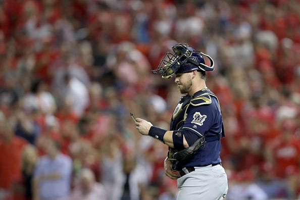 Milwaukee Brewers C Yasmani Grandal looks at his notes during a mound visit.