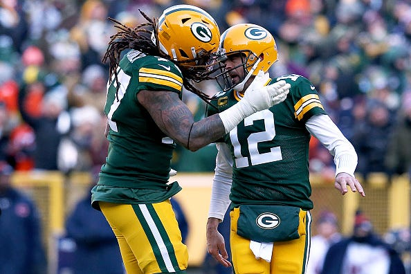 Packers QB Aaron Rodgers bangs heads with OT Billy Turner.