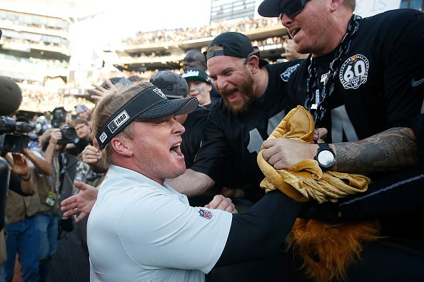 Jon Gruden celebrates a victory with Raiders fan.