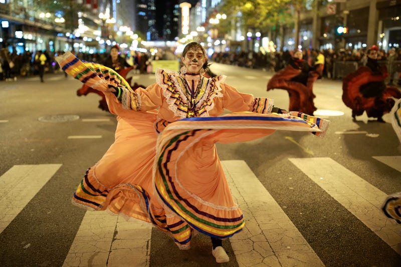 A woman parades and dances in traditional Dia de los Muertos makeup during the Chicago Halloween parade