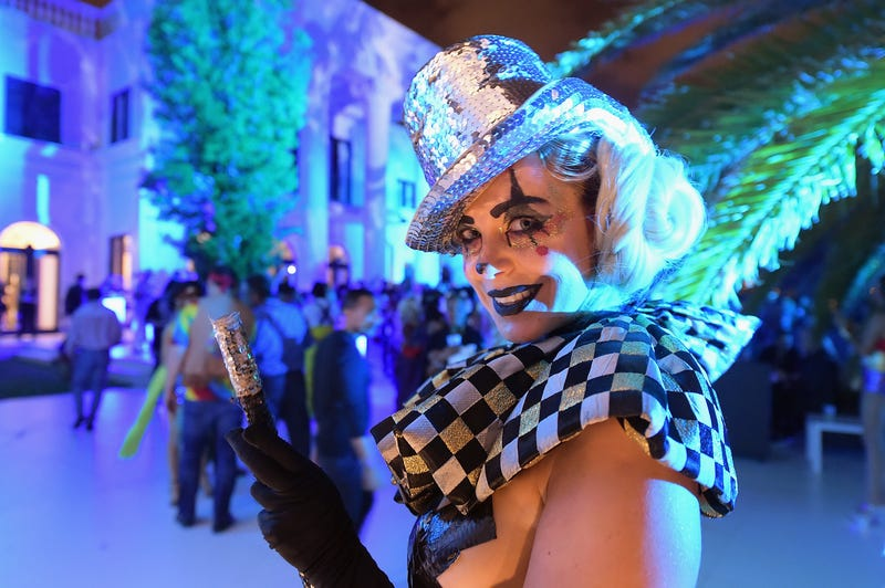 A woman poses in decorative make-up, checkered top and hat in front of a crowd at a Miami Beach party