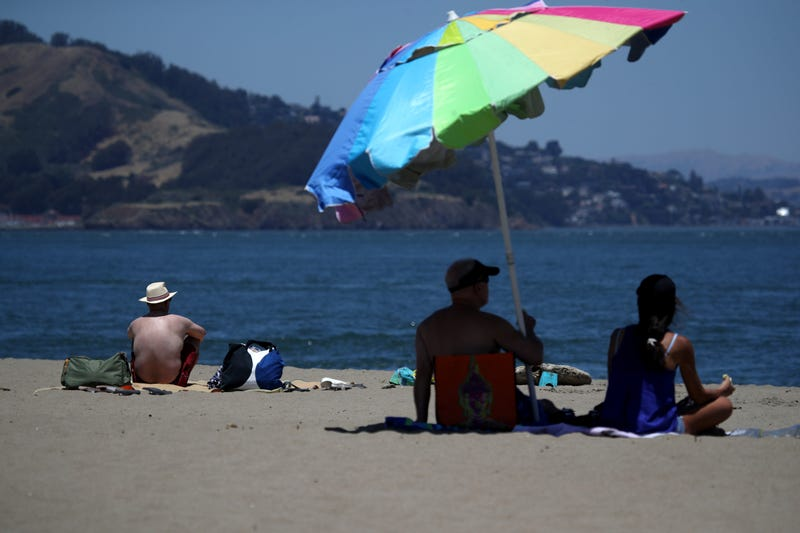 People sit on the beach at Crissy Field, June 2019