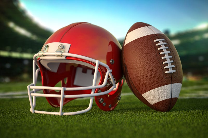 football ball and helmet on the grass of football arena or stadium
