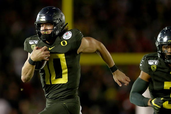 Oregon QB Justin Herbert rushes with the ball.