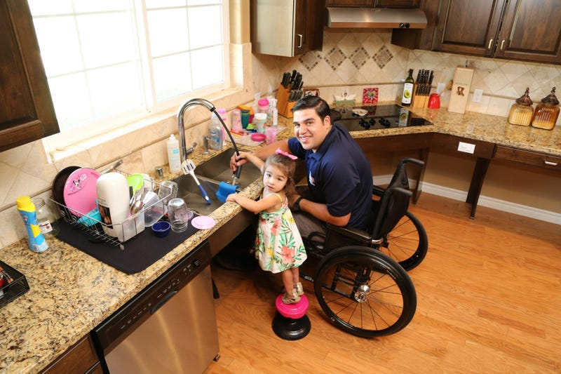 A wounded combat veteran who received a house from Homes For Our Troops washes dishes with his daughter