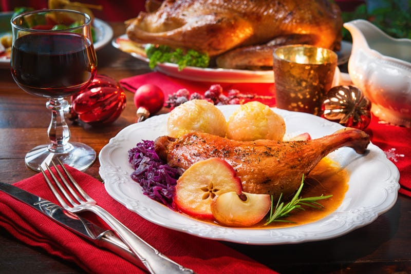 A turkey leg with fixins on a plate beside cutlery, a glass of wine, and Christmas ornaments
