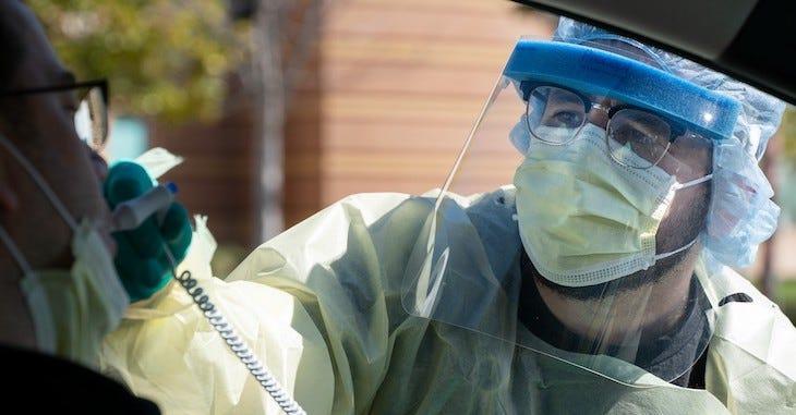 ICT Daniel Mendoza takes a veteran's temperature in a drive-thru COVID-19 screening.