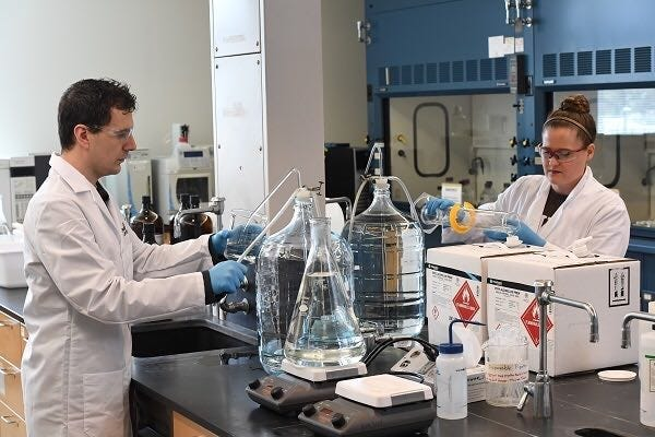 Rowan University chemistry professor Jim Grinias and his wife Kaitlin, a chemist at a pharmaceutical company, produced buckets of hand sanitizer that Rowan donated to Cooper Medical School.
