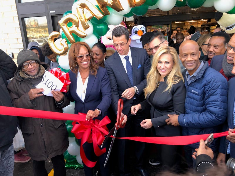 The owners of Local Market, Eva and Cezar Jakubowskicut a ribbon Wednesday opening the new store, located at 71stand Jeffery, as hundreds waited outside in the cold - some for many hours for free groceries.