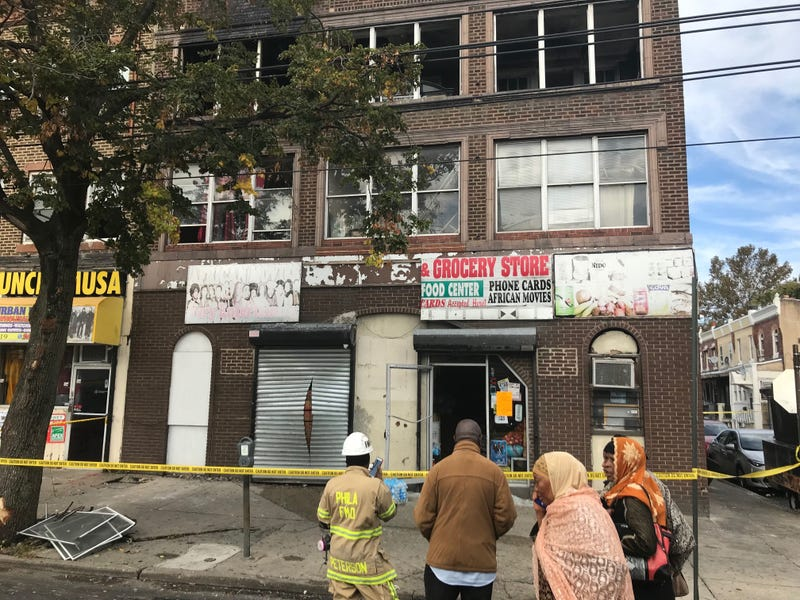 Firefighter and neighbors look on at the aftermath of a fatal fire on the 6500 block of Woodland Avenue.