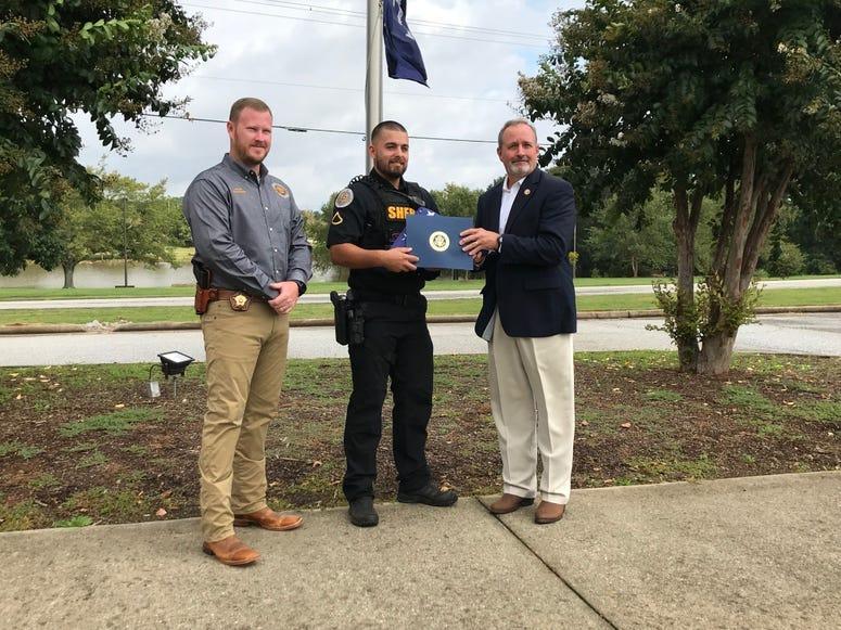 Duncan presents flag to Sheriff Chad McBride (left) and Roscoe's handler Master Deputy Matt Davis (middle) - Emily Gill