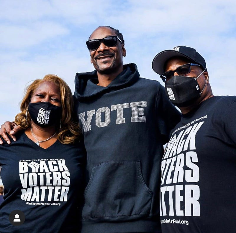 Black Voters Matter Fund co-founders LaTosha Brown (l) and Cliff Albright (r) with Snoop Dogg during a recent voter registration even in California