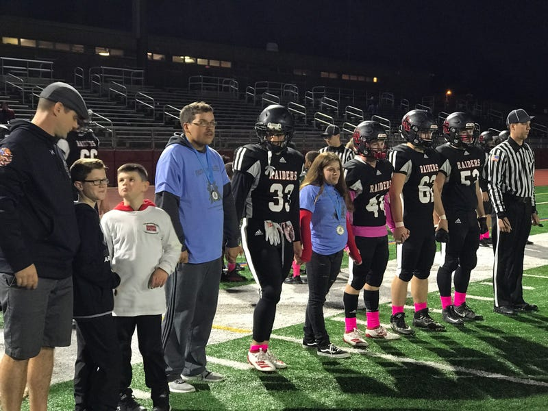 Alivia Sciarra standing alongside members of the Archbishop Ryan High School football team. Sciarra, who has special needs, got to be an honorary captain, and was named honorary homecoming queen as well.