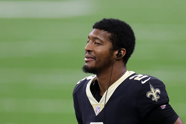Jameis Winston smiles on the sideline with the New Orleans Saints.