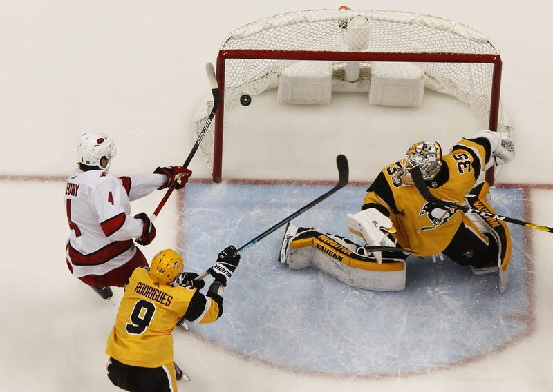 Carolina Hurricanes defenseman Haydn Fleury (4) attempts to tip the puck past Pittsburgh Penguins goaltender Tristan Jarry (35) as Pens center Evan Rodrigues (9) defends during the second period at PP...