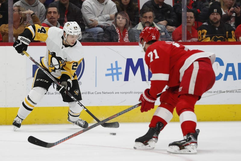 Pittsburgh Penguins center Dominik Kahun (24) skates with the puck defended by Detroit Red Wings center Dylan Larkin (71) in the third period at Little Caesars Arena.