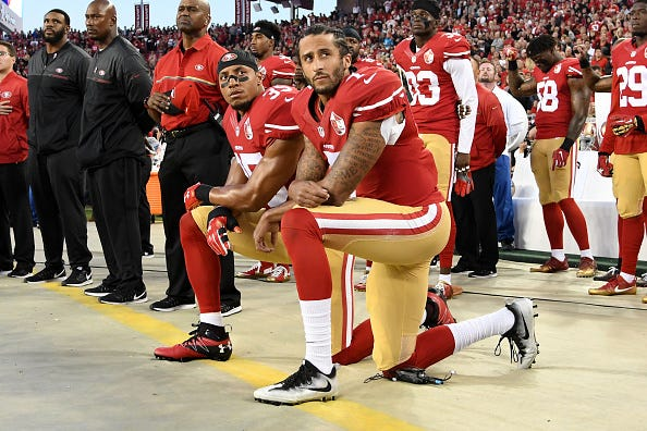 Colin Kaepernick kneels in protest during the national anthem.