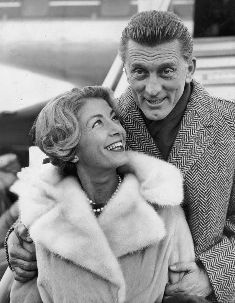Kirk Douglas and his wife Anne Budyens arriving in London for the premiere of his new film, 'Spartacus' on Dec. 5, 1960 (Photo by Dennis Oulds/Central Press/Getty Images)