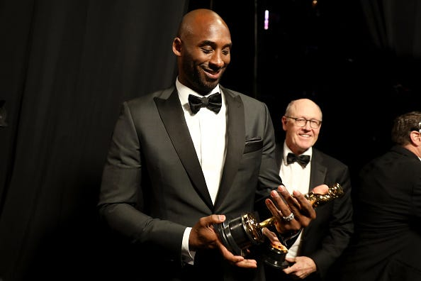 Kobe Bryant admires the Oscar he won in 2018.