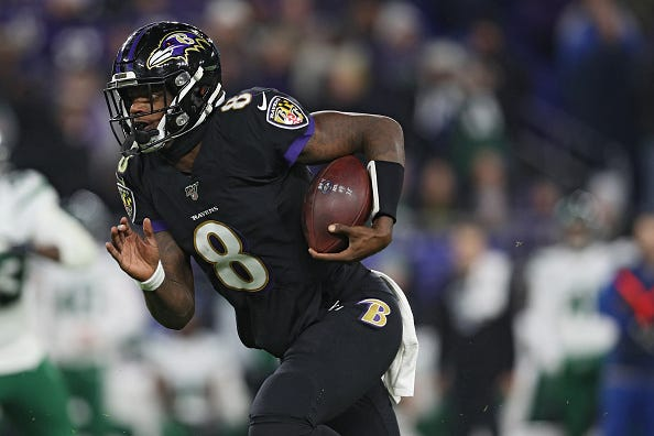Lamar Jackson rushes with the ball for the Ravens.