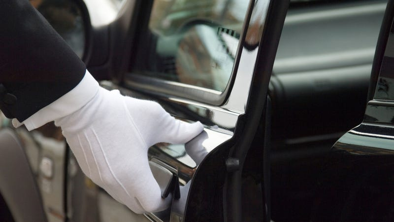 A white gloved hand opens a limousine door