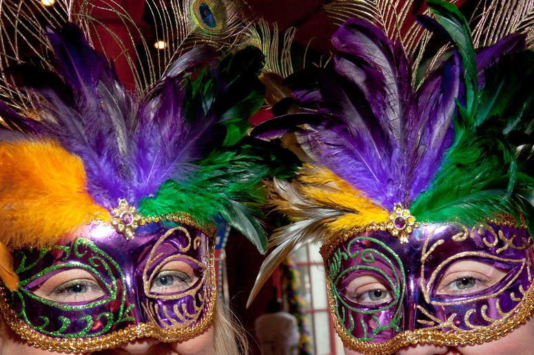 Women wearing purple, gold and green masks for Mardi Gras