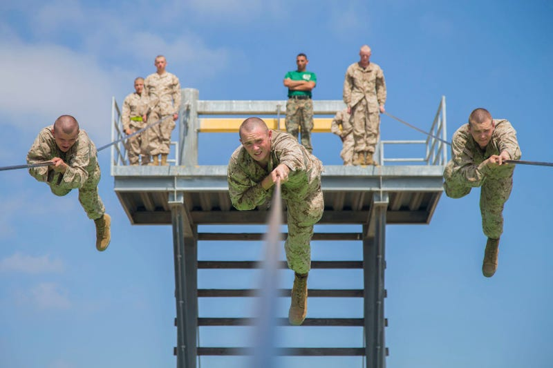 Marine recruits participate in the Slide for Life obstacle on a confidence course at Marine Corps Recruit Depot San Diego