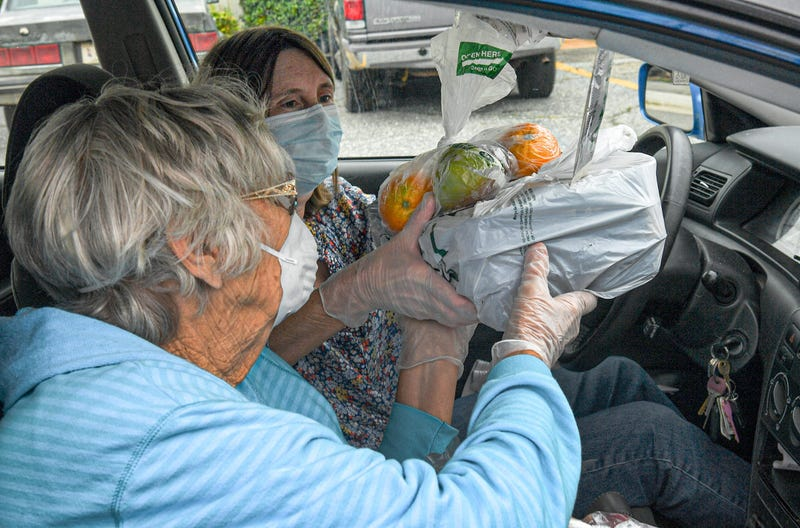 Shirley Mayfield, left, of Anderson hands meals to driver Sharon Williford of Starr, from Southern Way Catering in Greenville in line at a Meals on Wheels Anderson distribution at the Homeland Park Water District parking lot in Anderson, S.C. Thursday, Ma