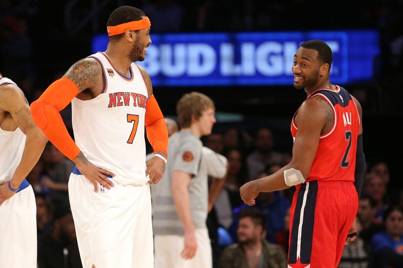 Carmelo Anthony chats with John Wall during a game.