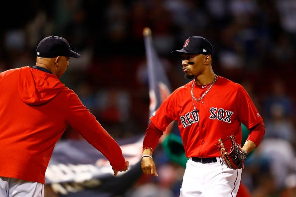 Red Sox OF Mookie Betts celebrates a victory with Alex Cora.