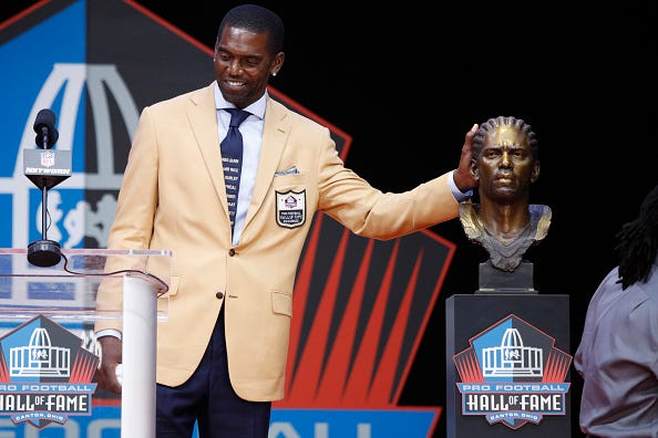 Randy Moss poses with his bust at the Pro Football Hall of Fame.