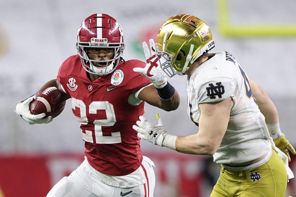 Najee Harris stiff arms a Notre Dame tackler
