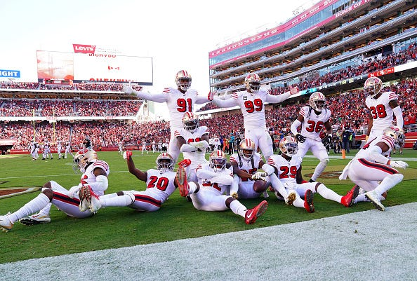 The San Francisco 49ers defense celebrates in the end zone.