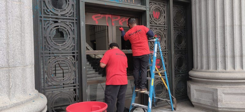 Workers repair smashed windows at Oakland City Hall.