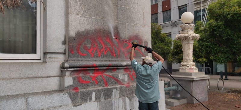Workers clean graffiti from Oakland City Hall.