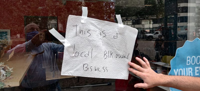 """A sign labels a business as """"black-owned"""" and calls for peace in Oakland"""