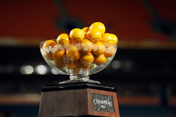 Oranges are placed in the Orange Bowl trophy.