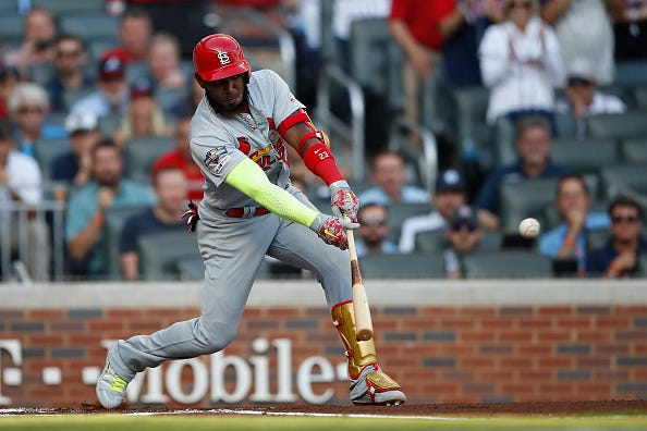 Marcell Ozuna swings at a pitch against the Braves in the NLDS.