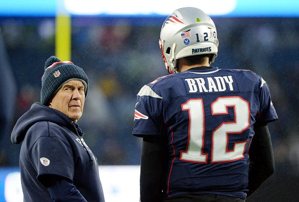 Bill Belichick glares behind him during a conversation with Tom Brady.