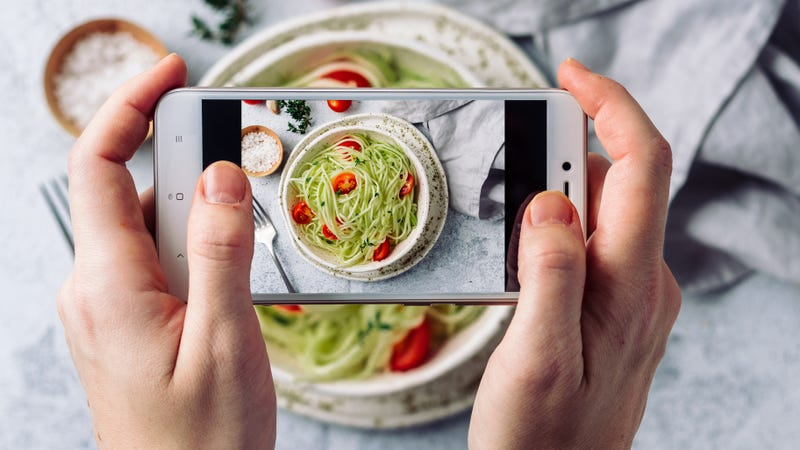 a person takes a photo with their phone of the food on a table