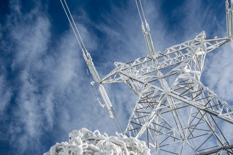 High voltage electric tower on a snowy day