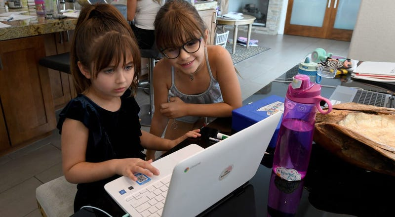 Two children sit in front of a computer doing their schoolwork.